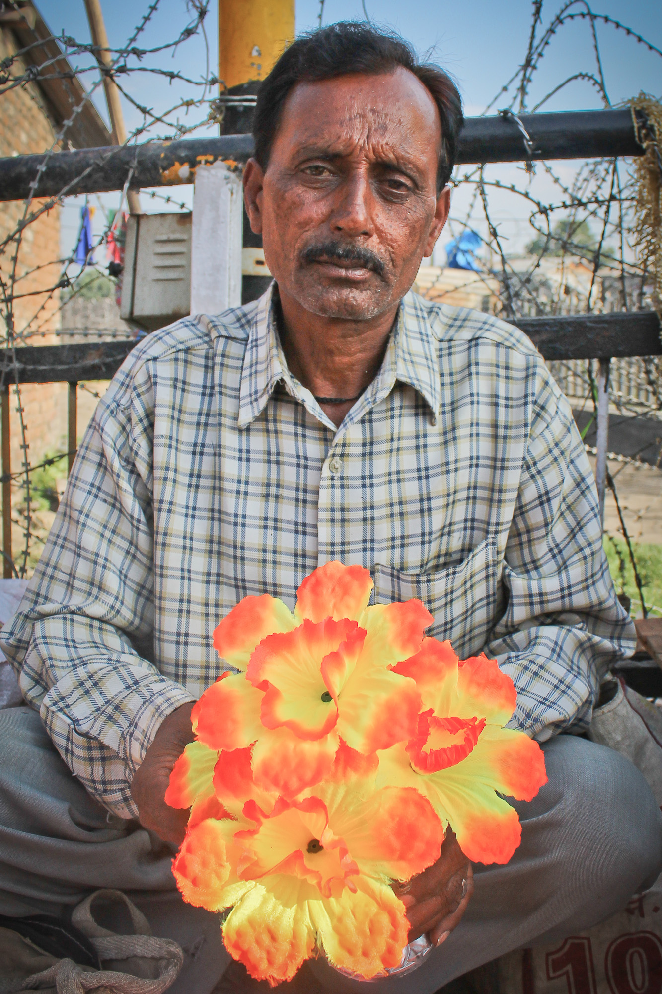 A man selling plastic flowers on a bridge in Srinagar. Back-dropped by razorwire and to his left is a brick building that houses an Indian official sitting on a 50. machine gun pointed ant the street.